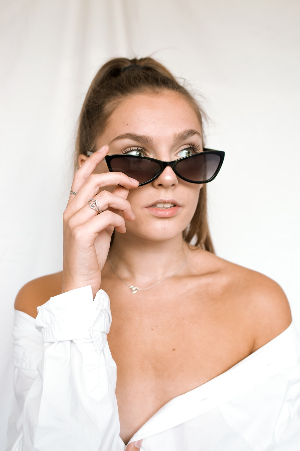 woman in white off shoulder top wearing black sunglasses