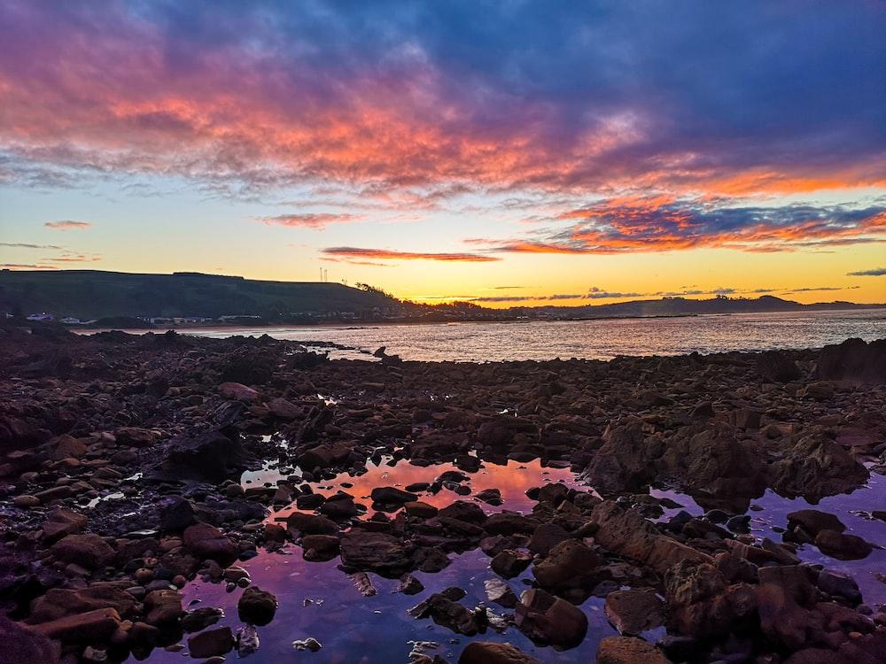 rocky shore under orange and blue sky