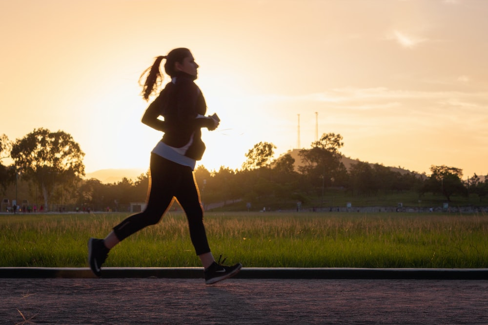 日没時に水の上を走っている黒いスポーツブラジャーと黒いズボンの女性