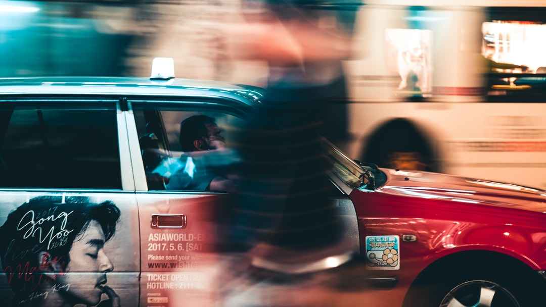 Man In Black and Red Striped Long Sleeve Shirt Driving Red Car - unsplash