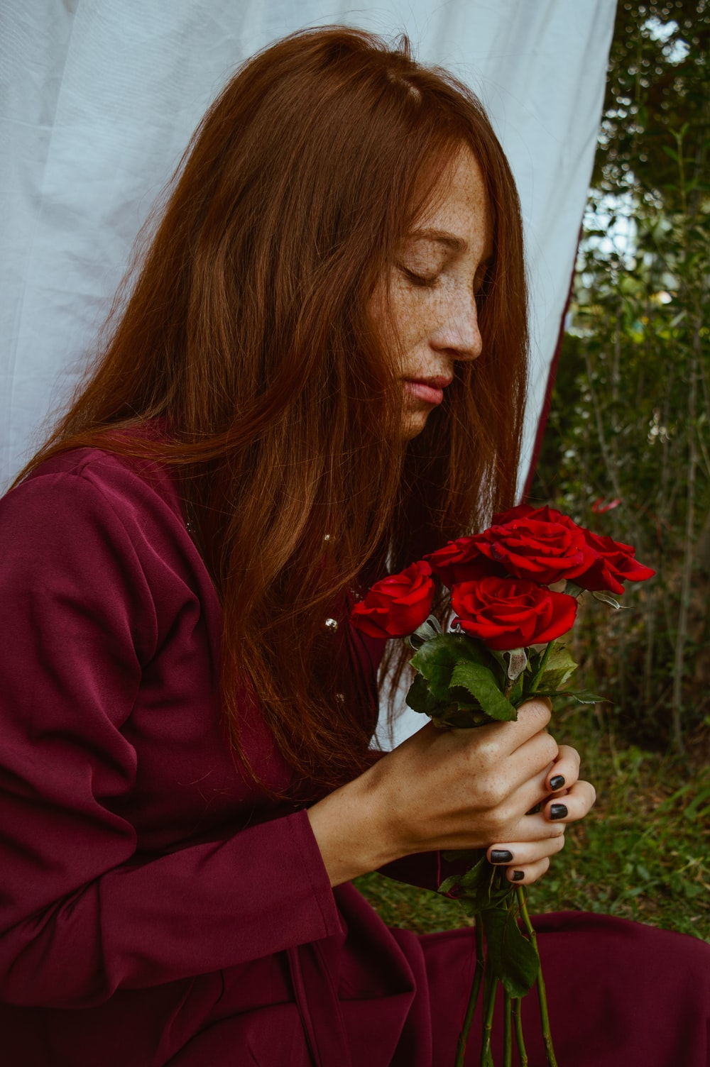 woman in red long sleeve shirt holding red rose