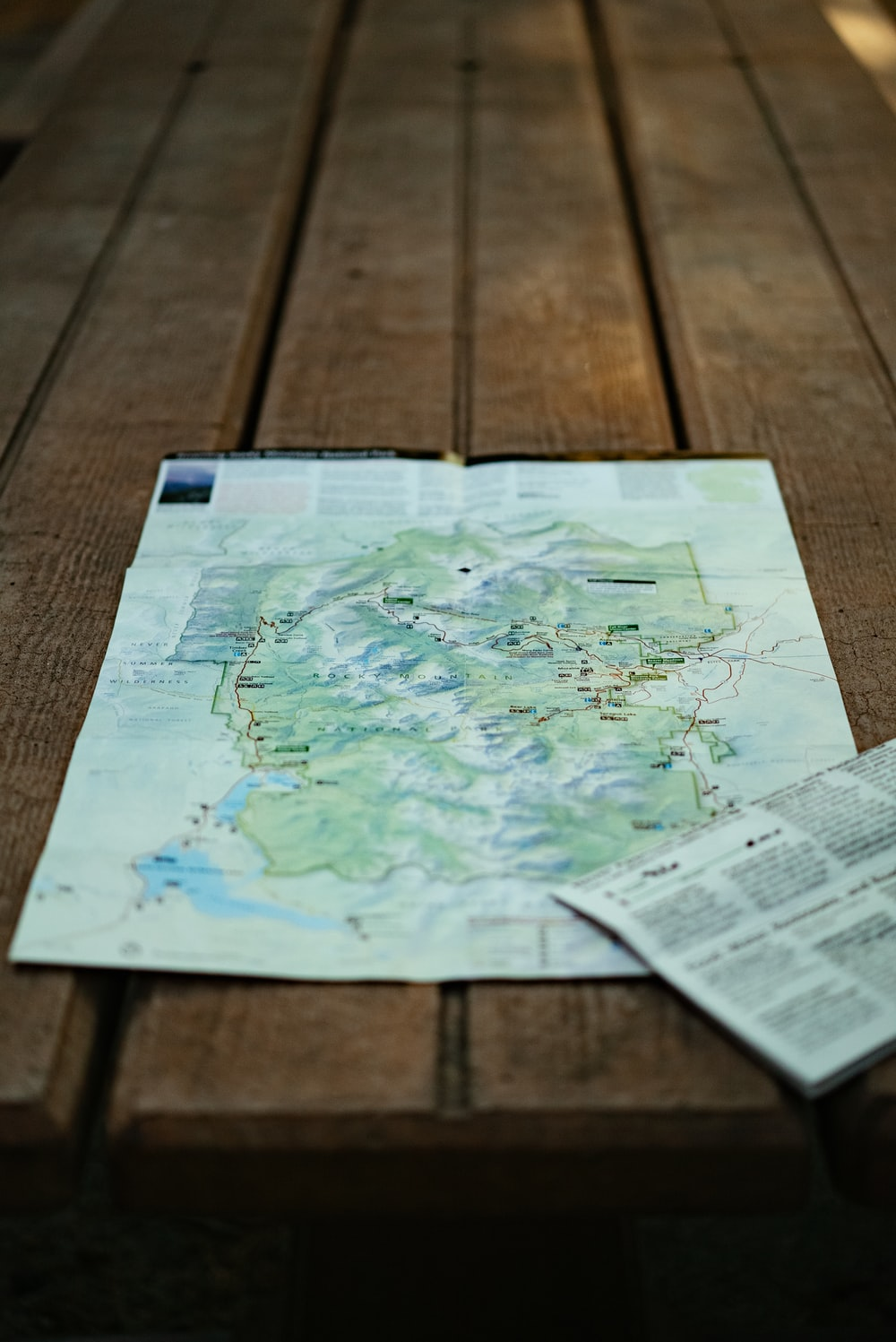 white and green map on brown wooden table