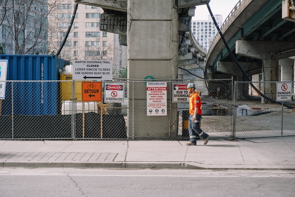 man in orange jacket standing on sidewalk during daytime