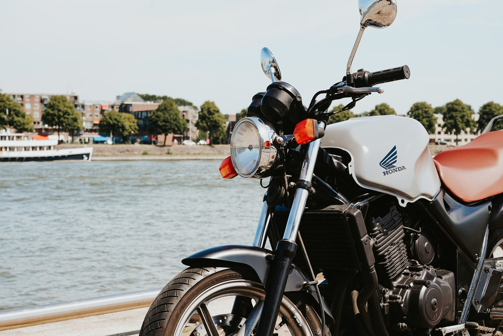 white and black motorcycle near body of water during daytime