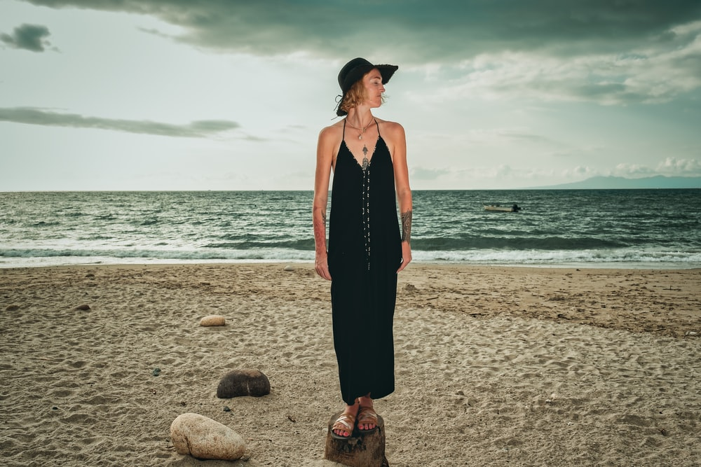 woman in black halter dress standing on beach during daytime