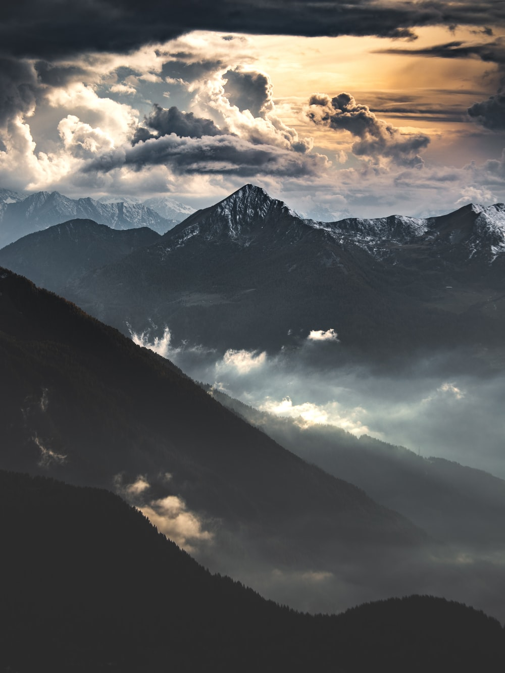 black and white mountains under cloudy sky during daytime