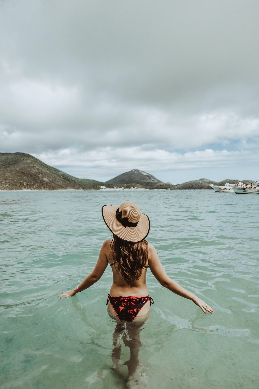 woman in red and white floral bikini wearing brown sun hat standing on sea water during