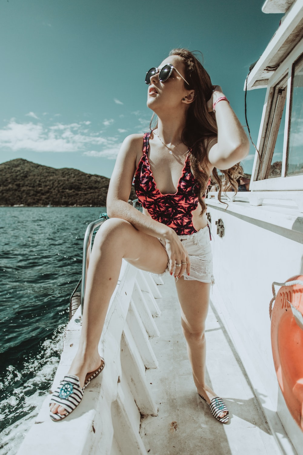 woman in red and white floral bikini sitting on white boat during daytime