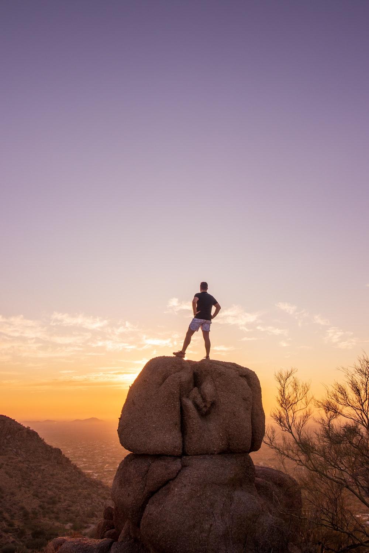 man standing on brown rock during daytime