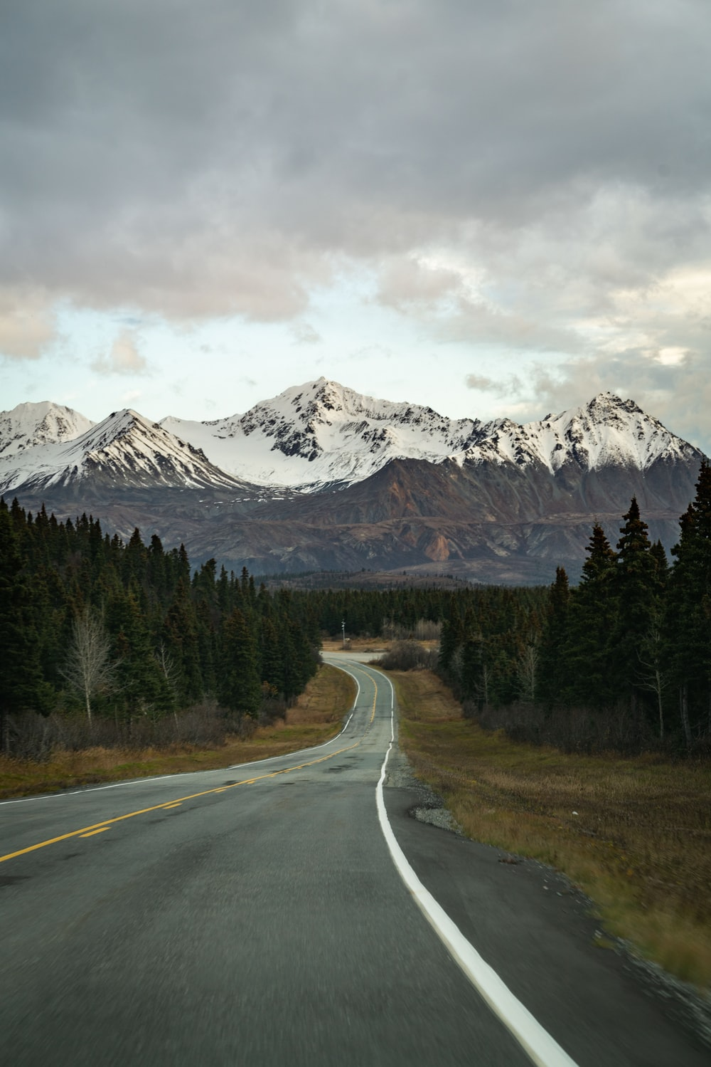 gray concrete road near green trees and snow covered mountain during daytime