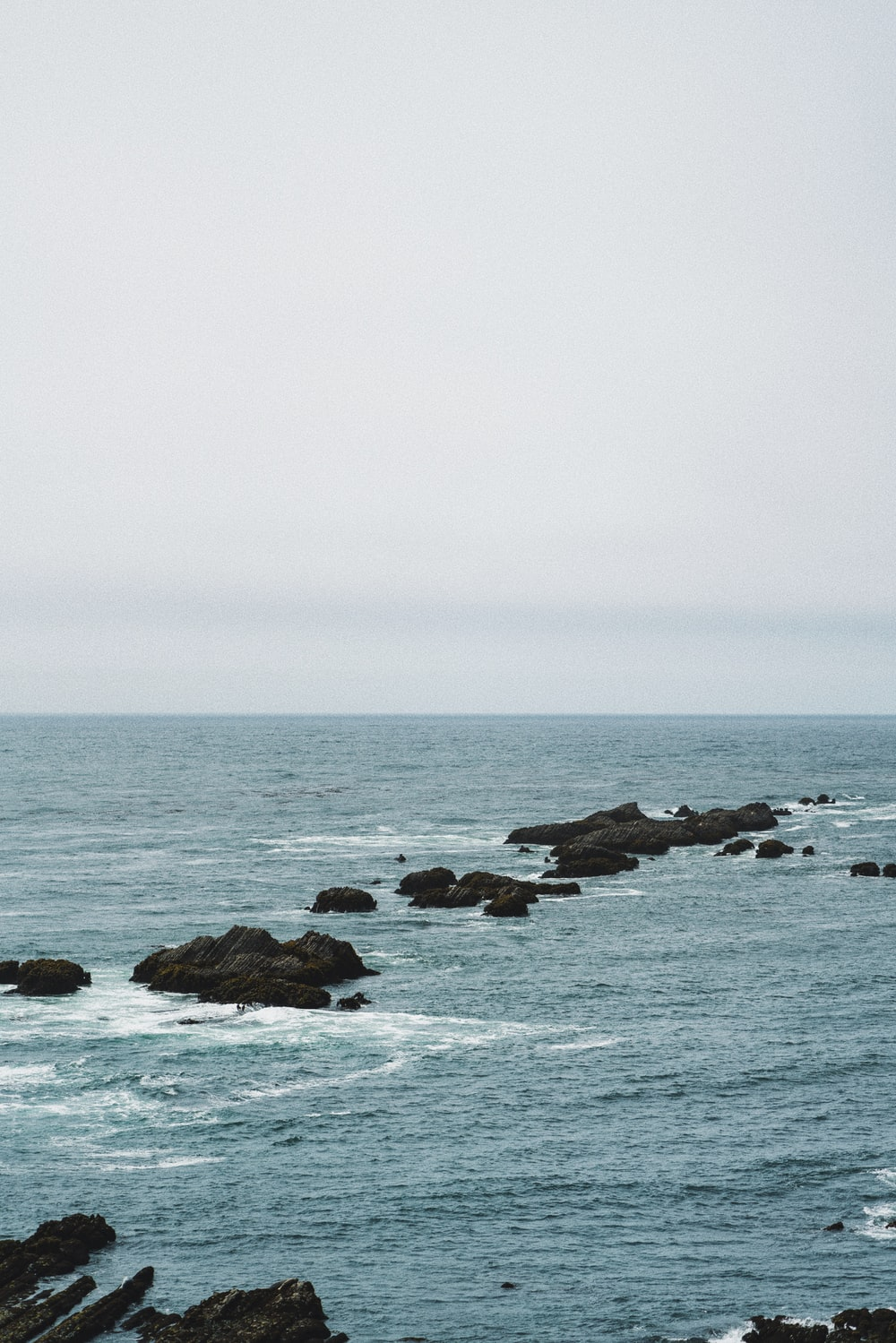 brown rock formation on sea under white sky during daytime