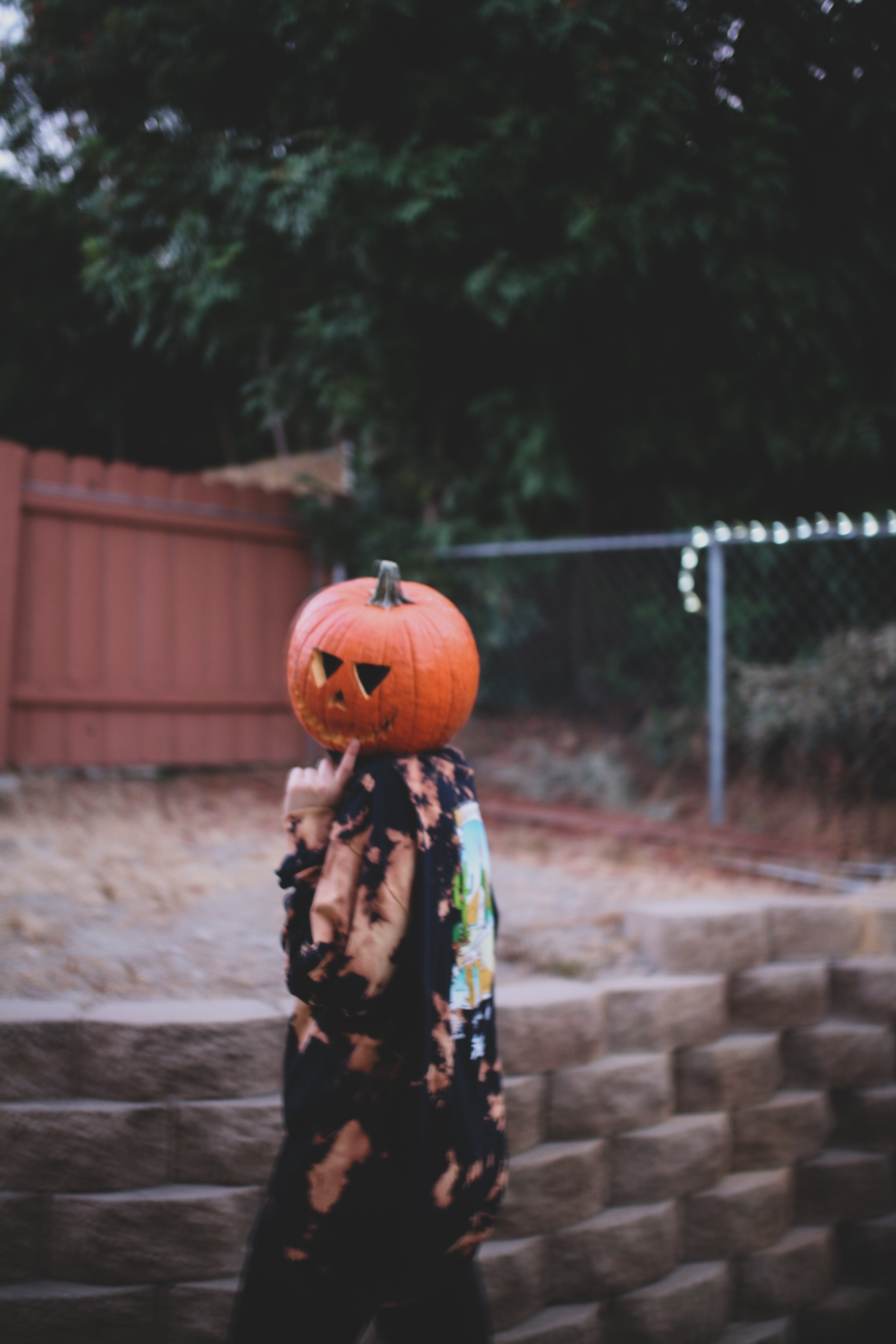 woman in black and white floral dress holding jack o lantern