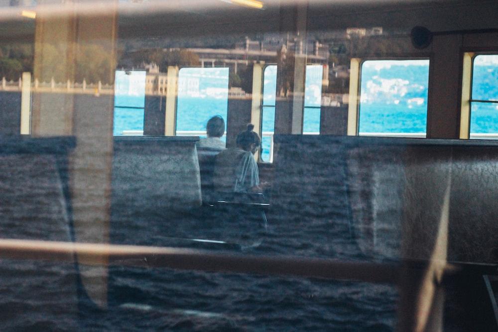 man in black jacket standing near glass window