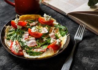 vegetable salad on red ceramic plate beside stainless steel fork