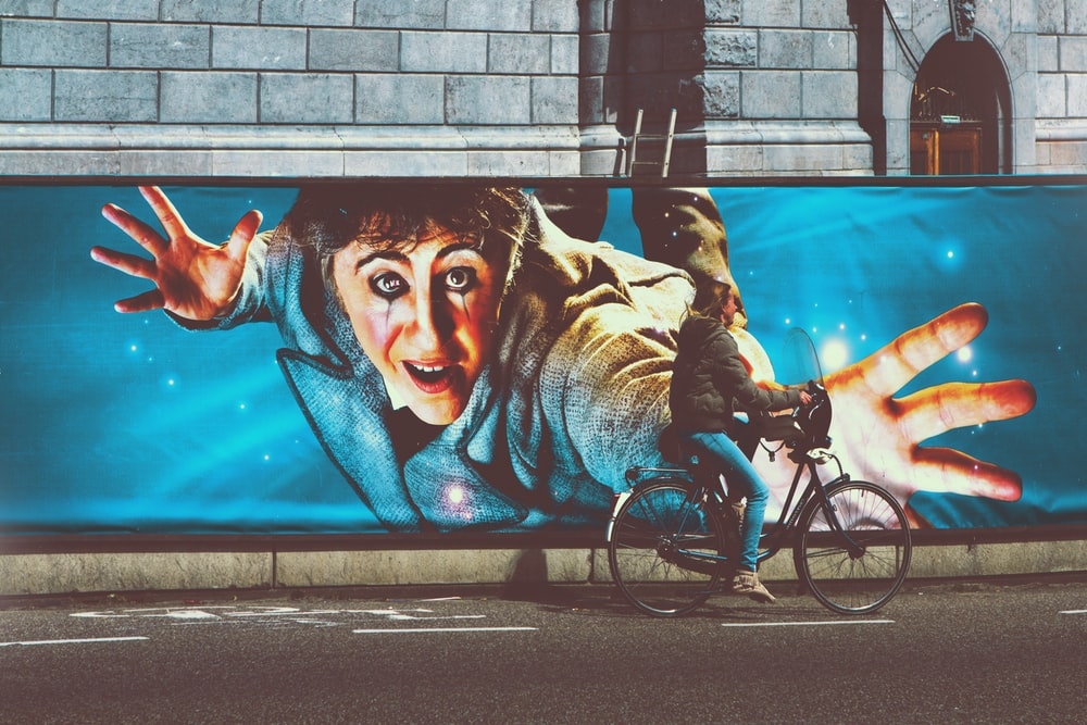 man riding bicycle with womans face graffiti