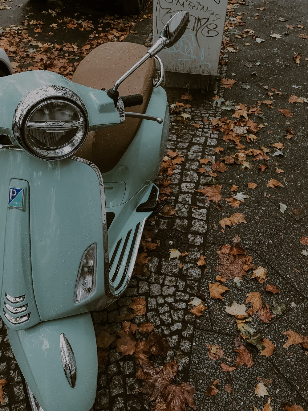blue and silver motor scooter on brown and gray concrete floor