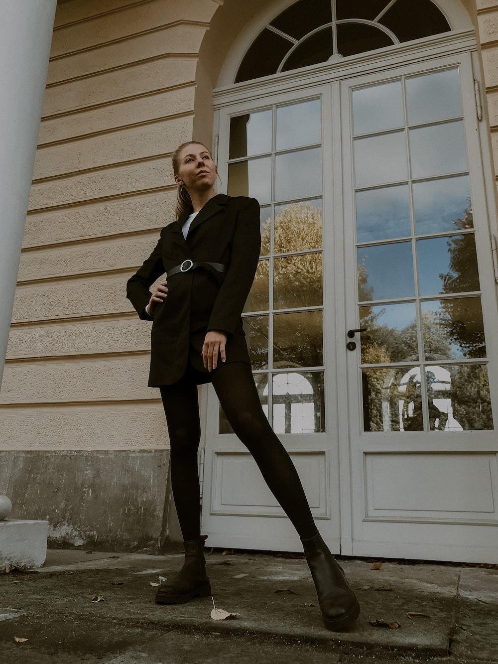 woman in black blazer and black dress pants standing beside white wooden framed glass window