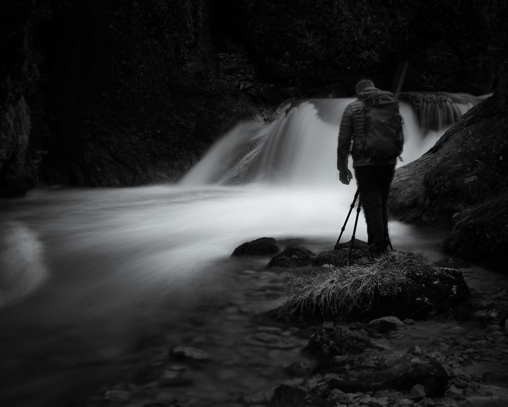 man in gray jacket standing on rock near waterfalls
