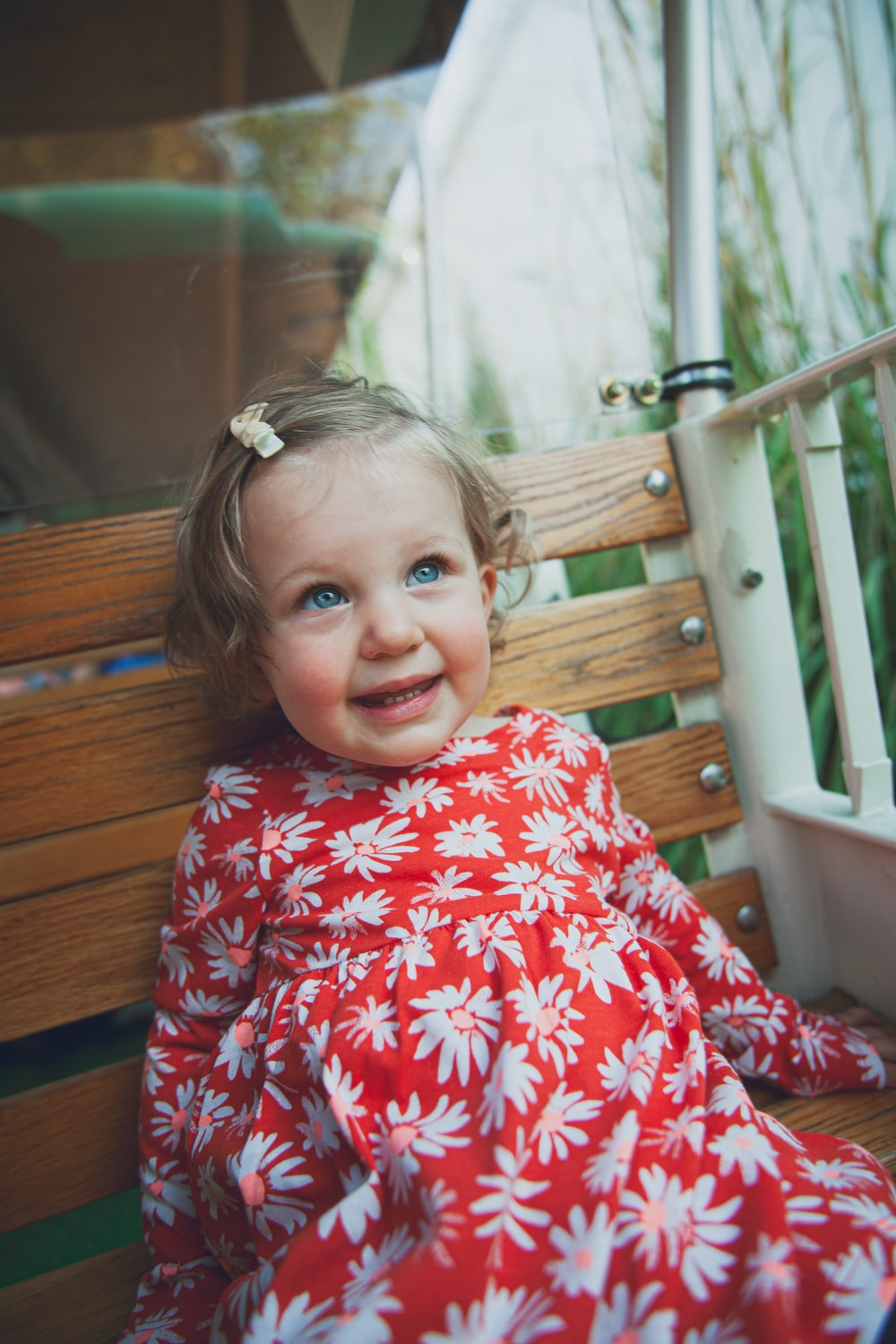 girl in red and white floral dress sitting on brown wooden bench