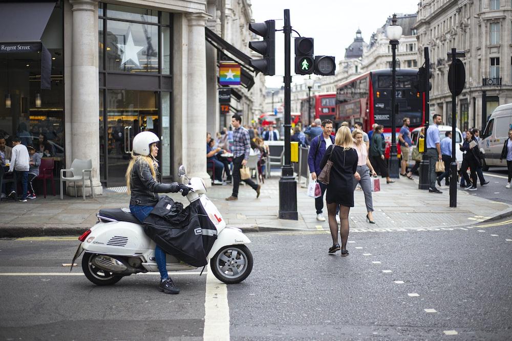 woman in black and white dress walking on sidewalk during daytime