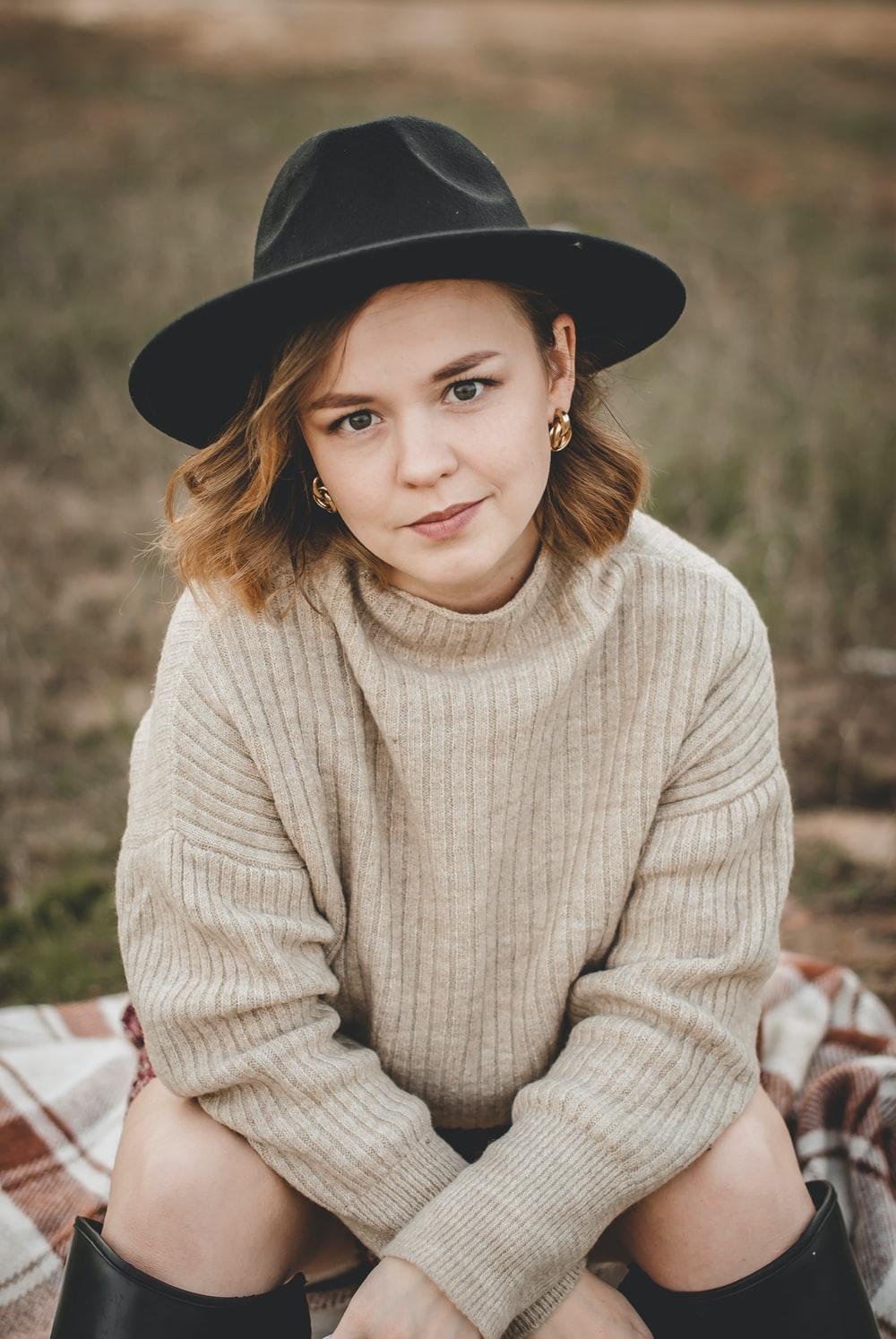 woman in beige sweater and black fedora hat