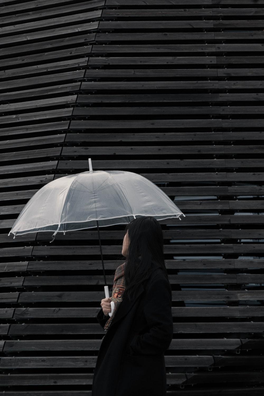 woman in black coat holding white umbrella