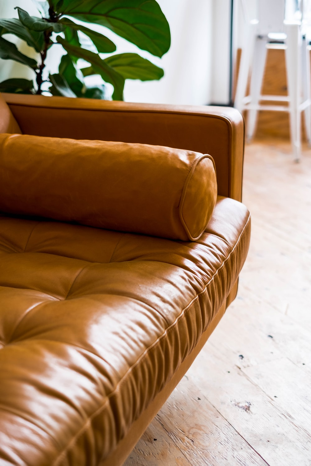 brown leather couch on white ceramic floor tiles