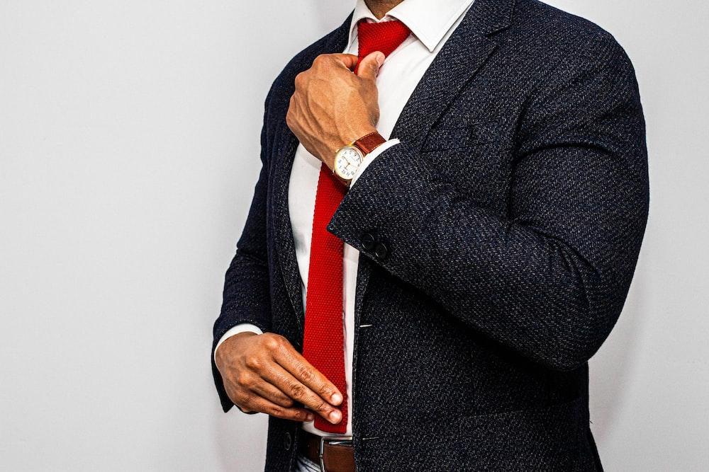man in black suit jacket and red necktie