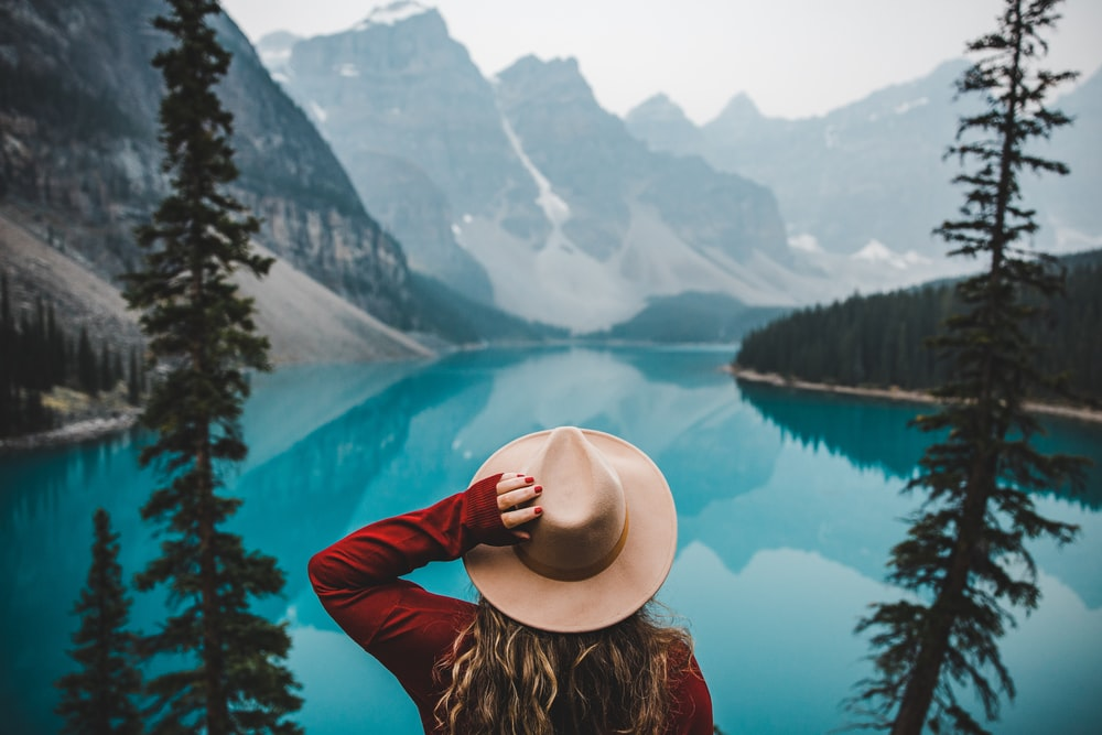 woman in brown sun hat and red long sleeve shirt sitting on rock near lake during