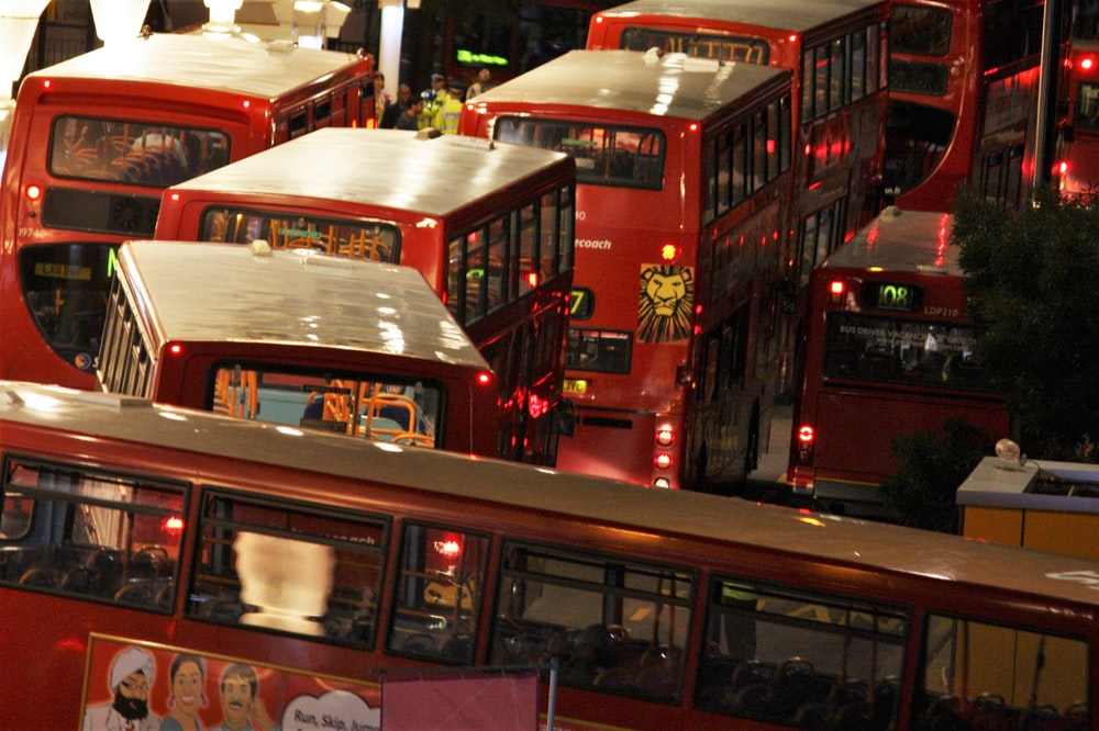 red double decker bus on road during nighttime
