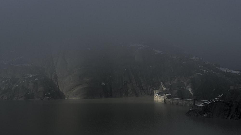 white ship on body of water near mountain during daytime