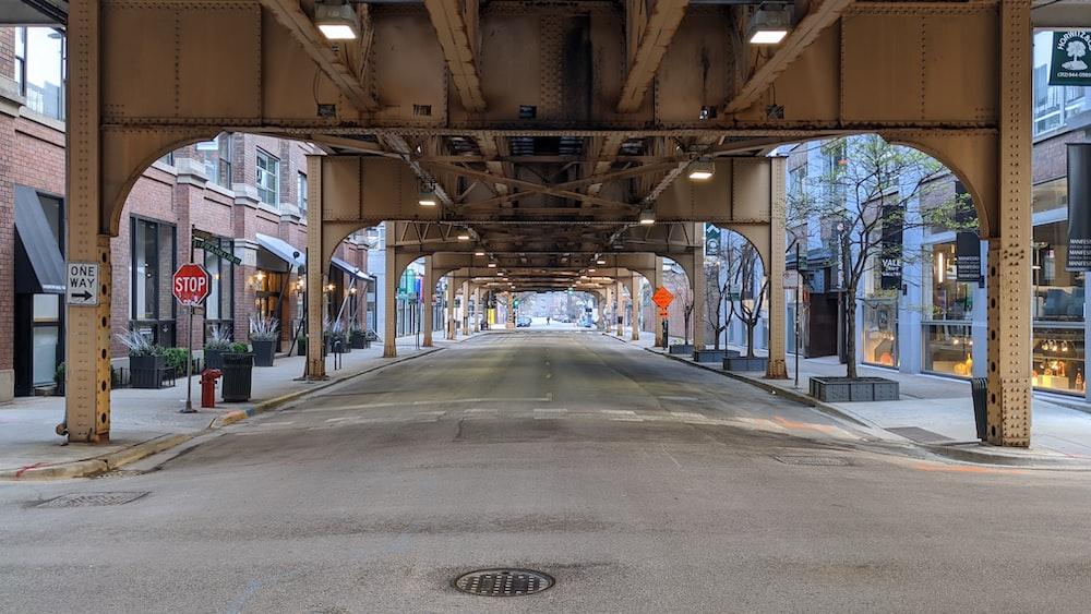 empty road in between buildings during daytime