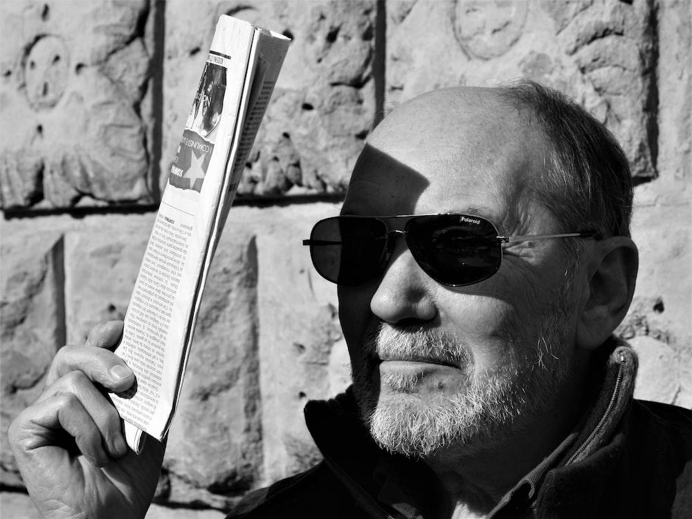 man in black sunglasses holding white box