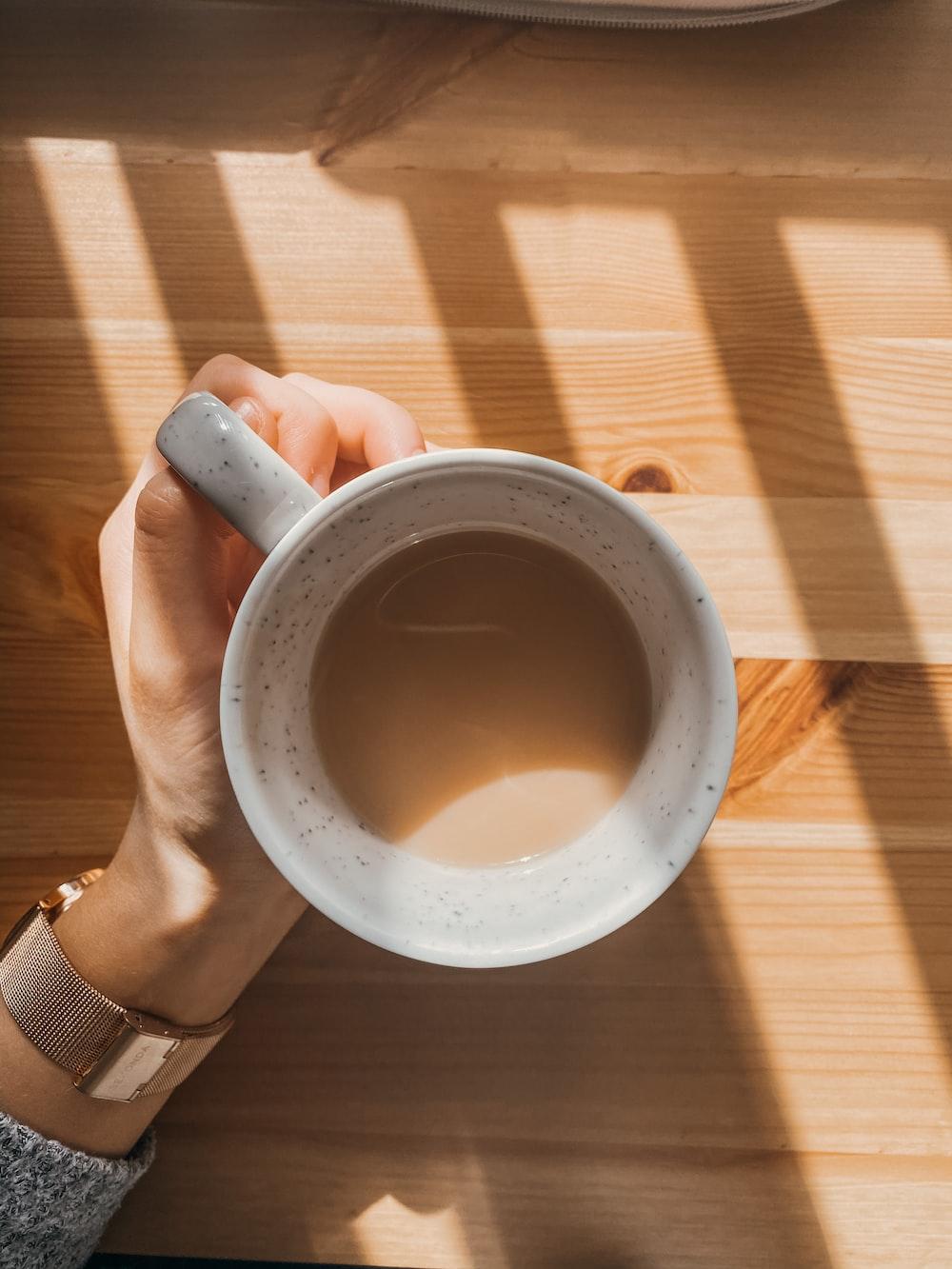 person holding white ceramic mug with black liquid
