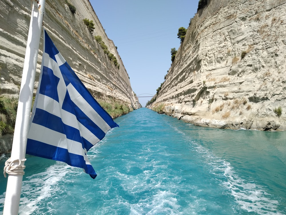 blue and white striped flag on rock formation near body of water during daytime