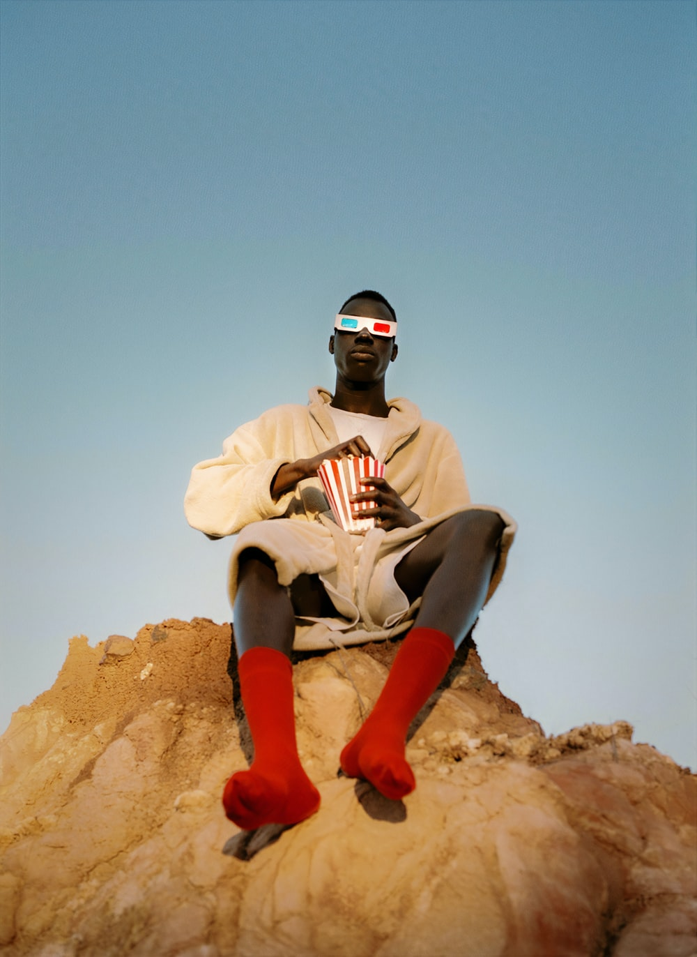 man in white and black stripe shirt and pants sitting on brown rock during daytime