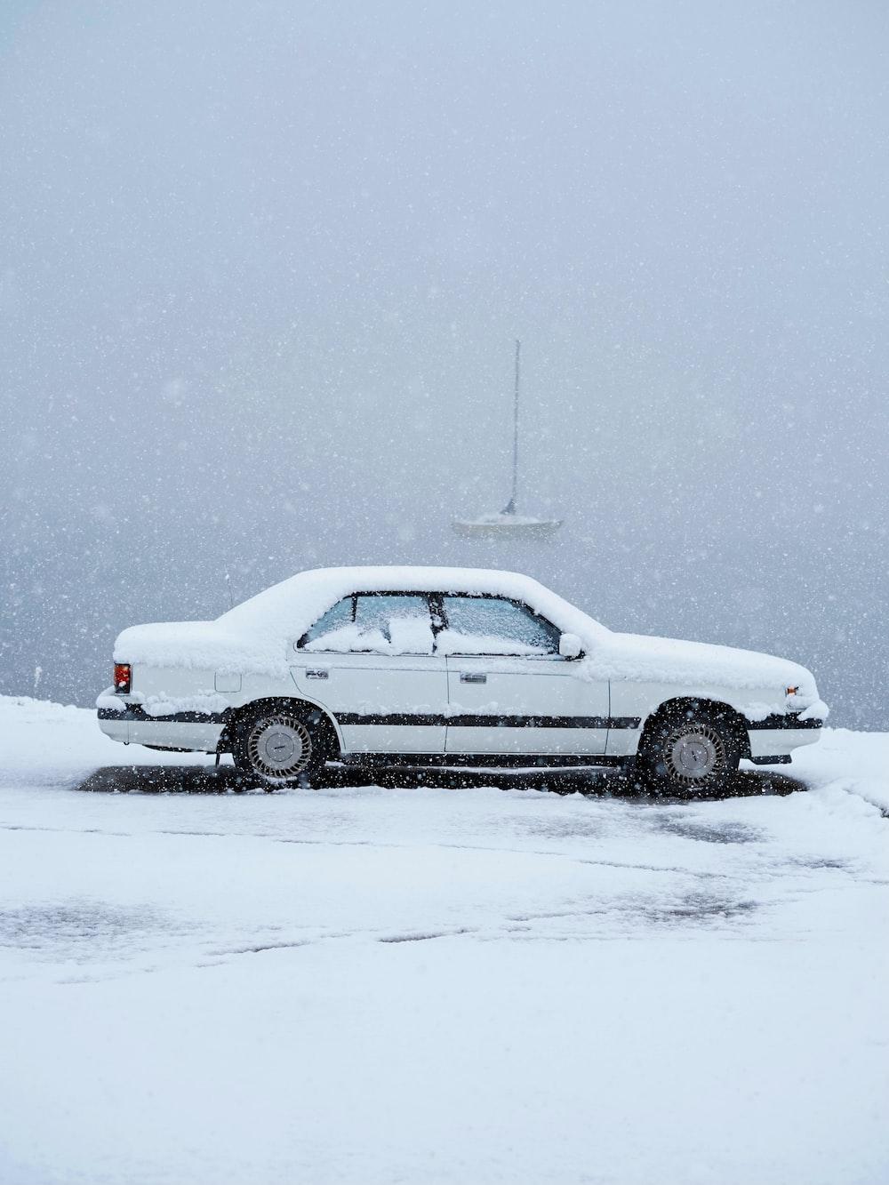 white sedan on snow covered ground
