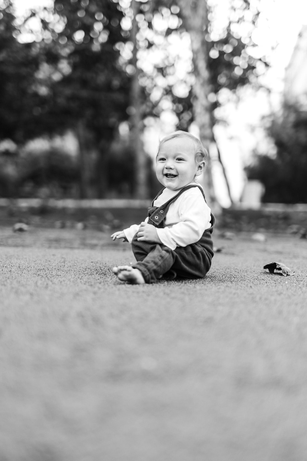 grayscale photo of child sitting on ground