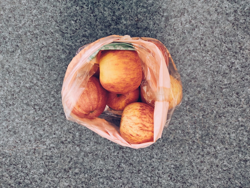 brown round fruits in brown plastic bag