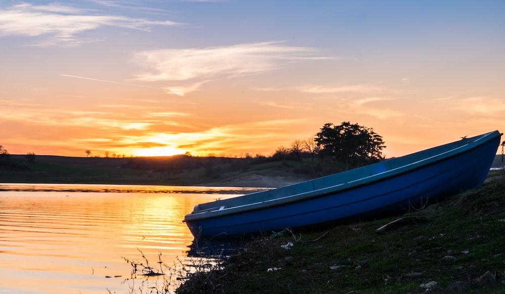 blue boat on lake during sunset