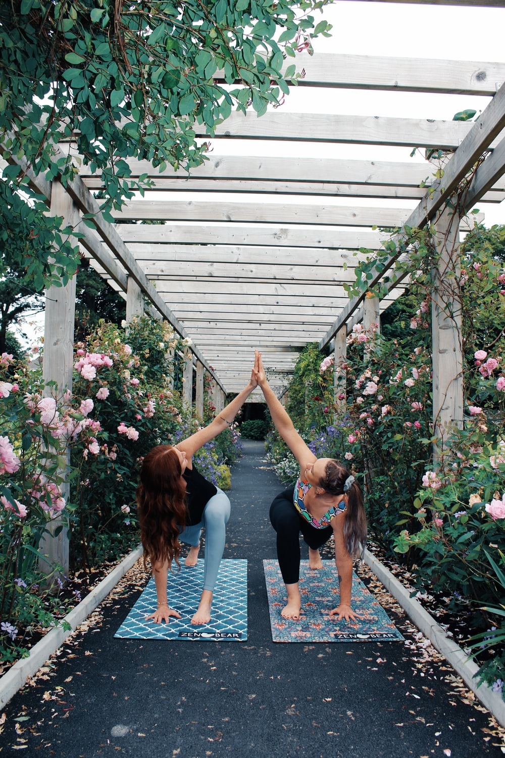 2 women in blue tank top and black leggings standing near pink flowers during daytime