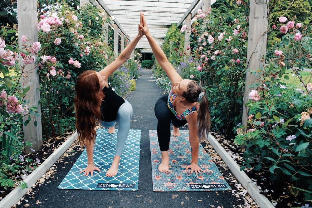 2 women in black tank top and black leggings doing yoga