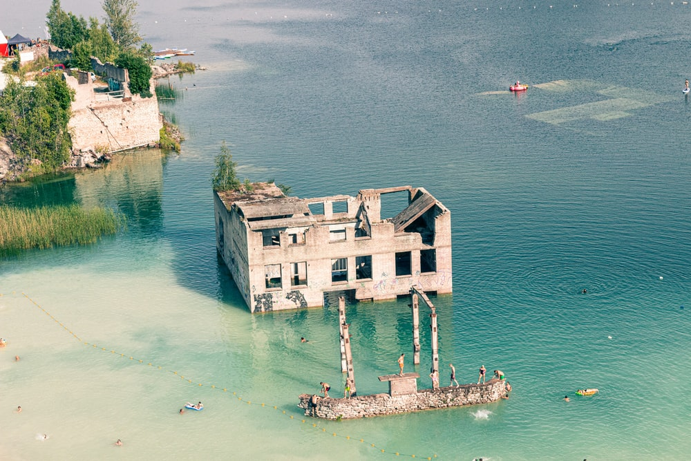white and brown concrete building on body of water during daytime