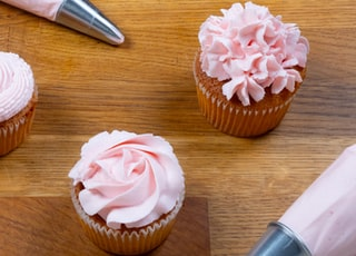 cupcake with pink icing on brown wooden table