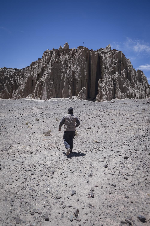 man in black jacket and blue denim jeans walking on white sand during daytime