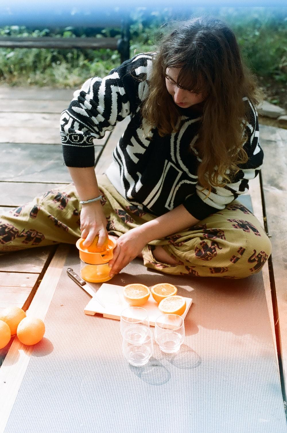 woman in black and white shirt holding orange fruit