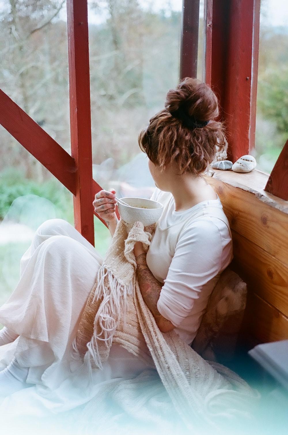 woman in white dress holding white ceramic mug