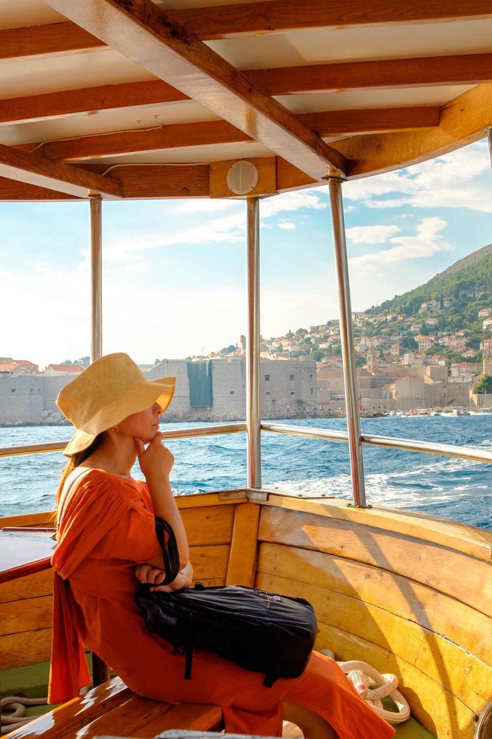woman in brown sun hat sitting on brown wooden boat during daytime
