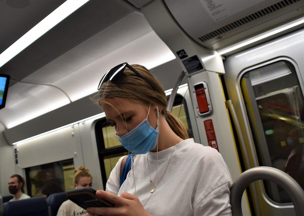 woman in white hoodie wearing blue headphones