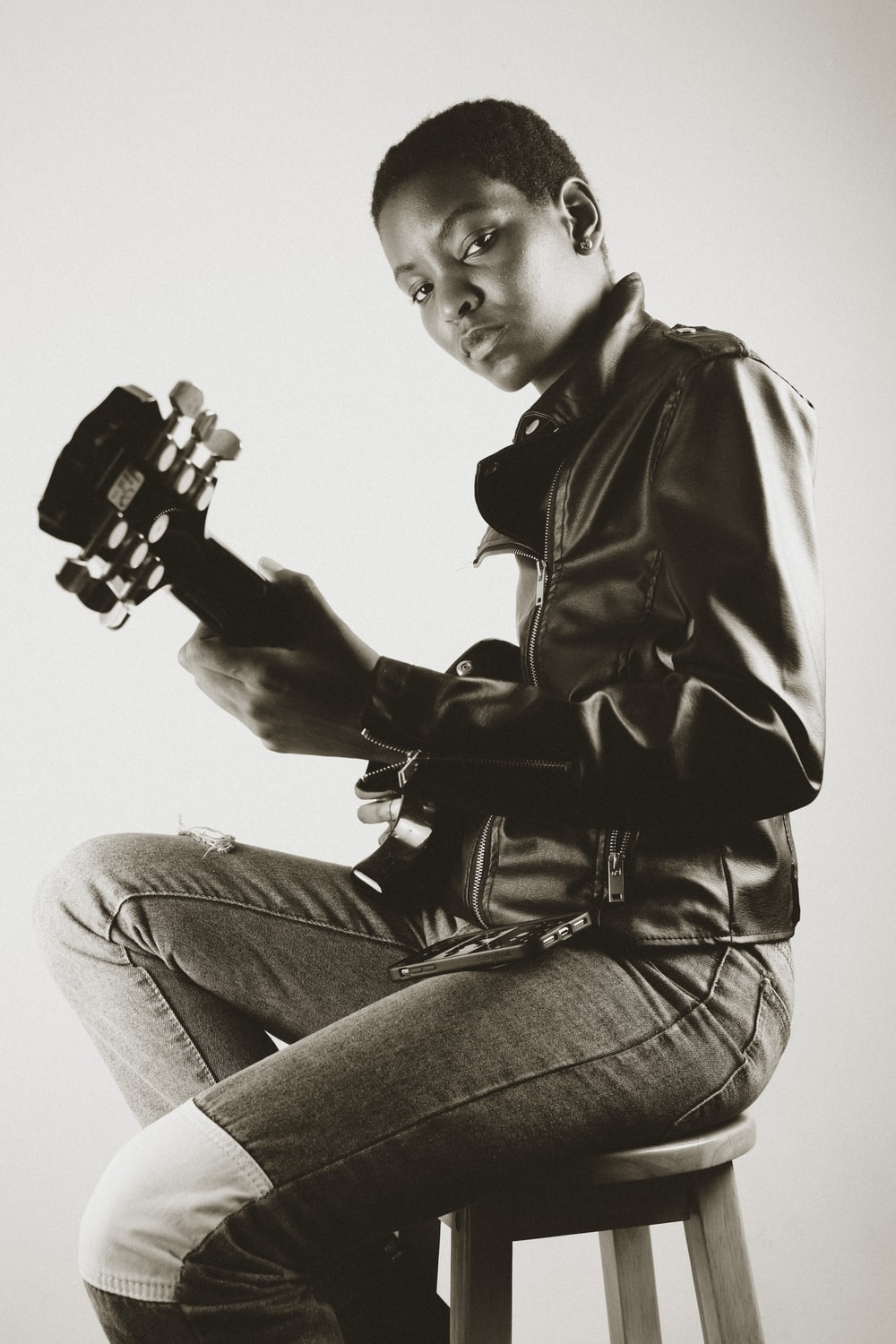 man in black leather jacket and gray denim jeans holding black and white game controller